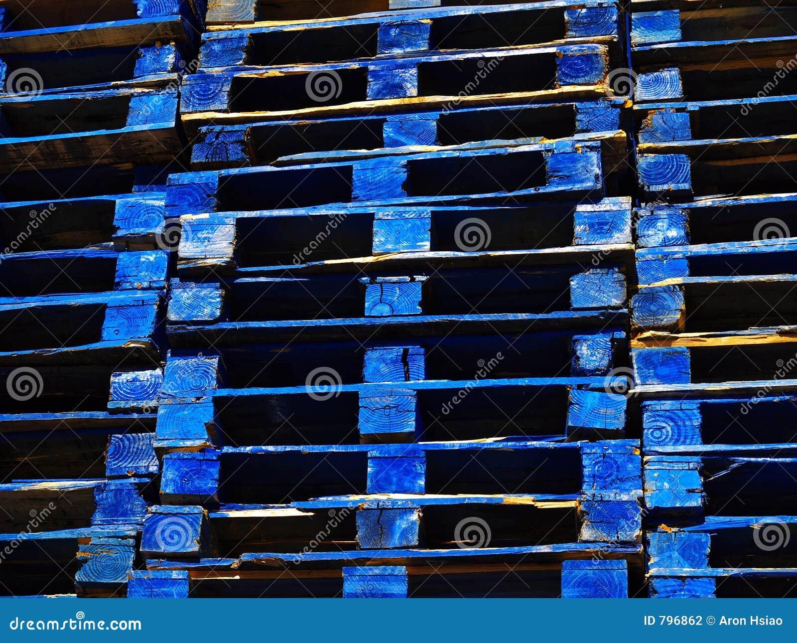 Heldere blauwe houten verschepende paletten