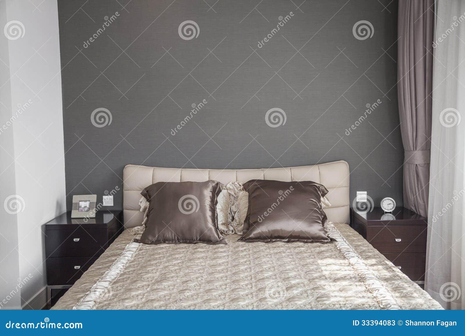 Heldere moderne slaapkamer met beige sprei. stock afbeelding