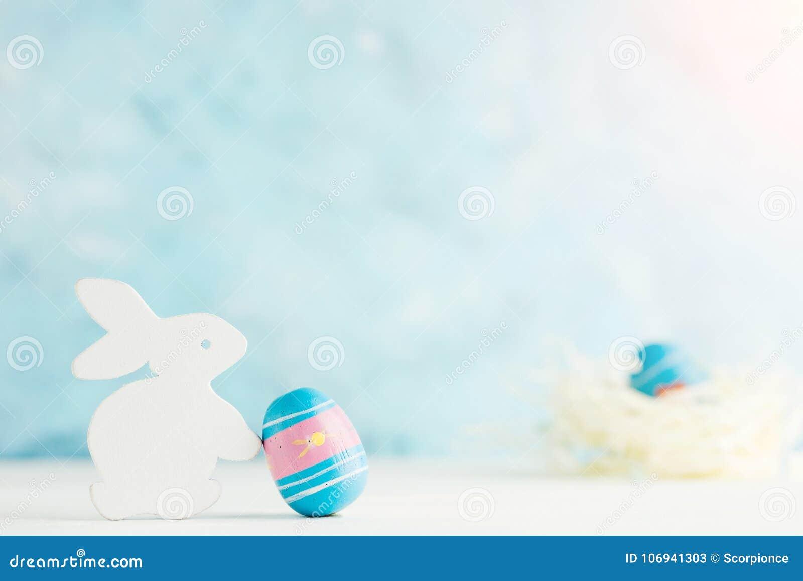 Heldere pasen achtergrond: het witte houten konijntje met paited ei