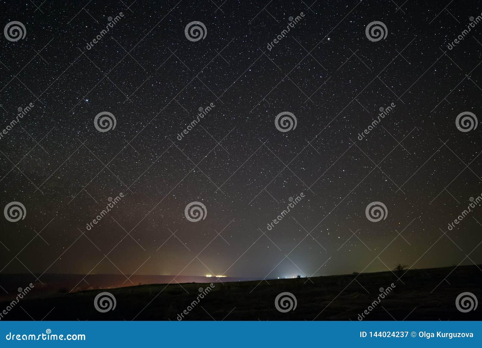 Heldere sterren in de nachthemel met verlichting van de straatlantaarns van de stad Lichte verontreiniging
