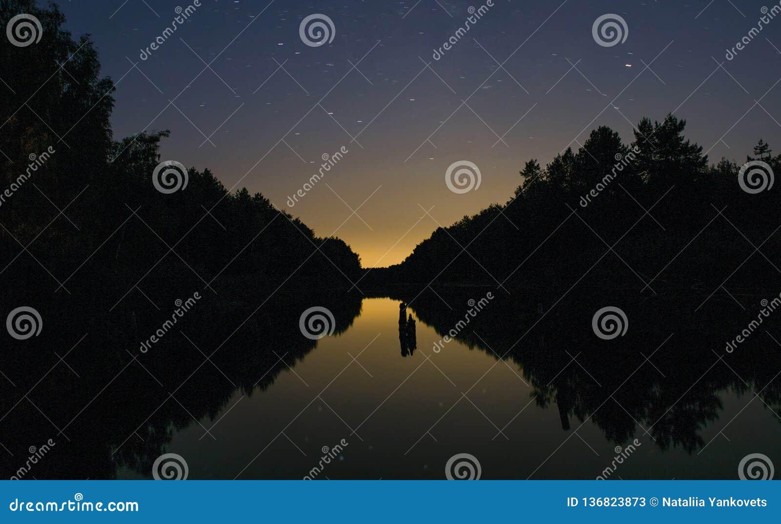 Heldere zonsondergang amid donkere hemel boven de Rivier in het bos