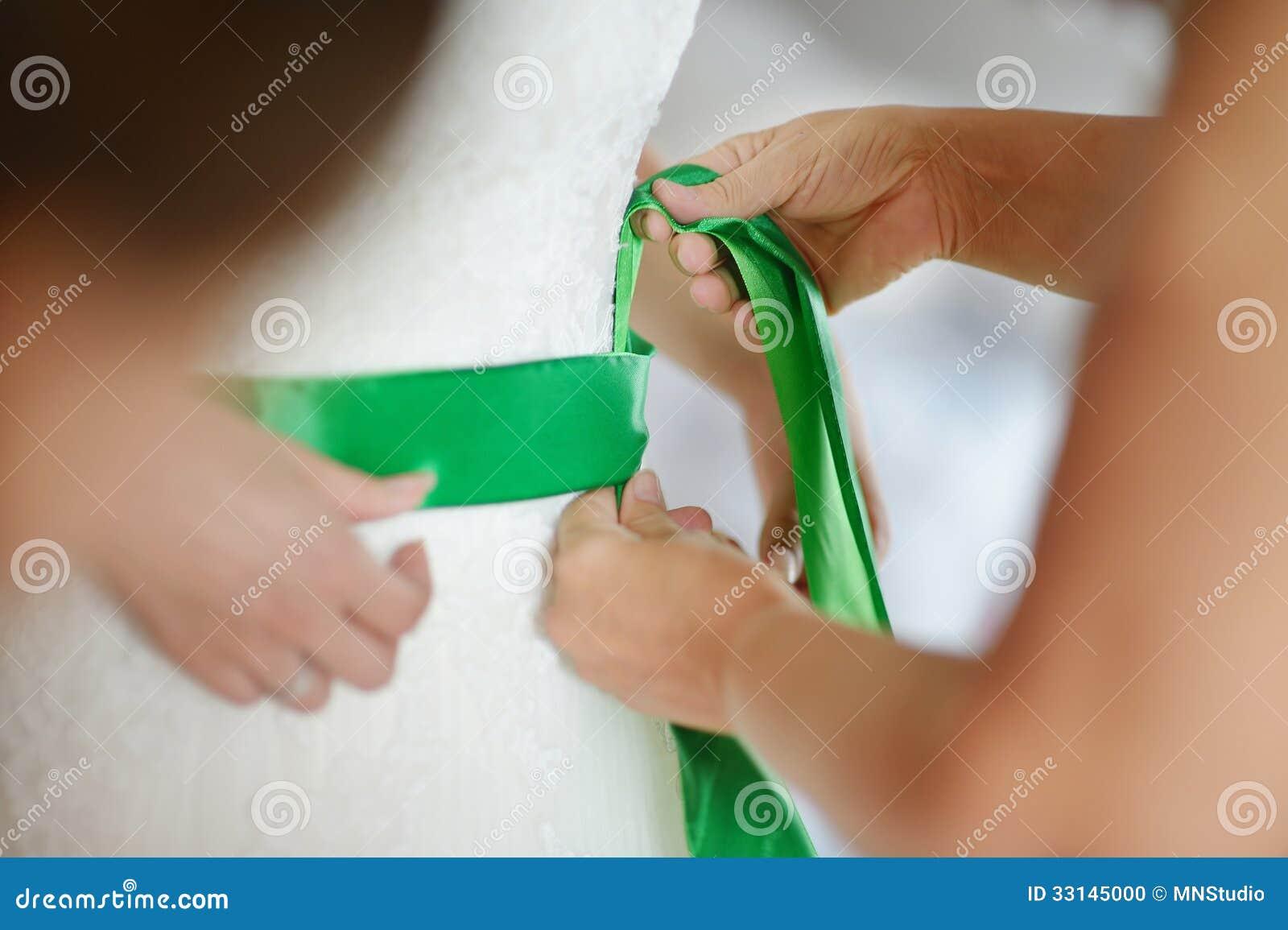 Helfen der Braut, ihr Hochzeitskleid zu setzen