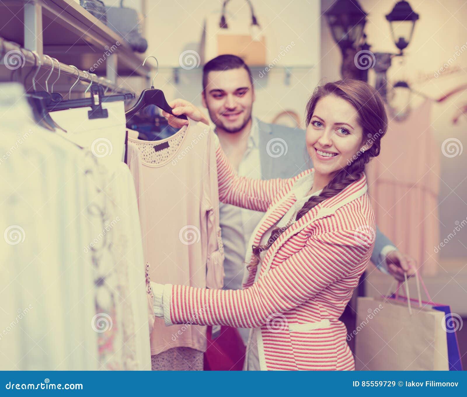 Helfende Frau des Ehemanns, zum von Kleidung zu wählen