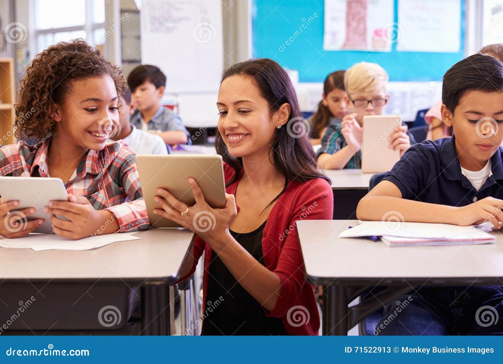 Helfende Kinder des Lehrers mit Computern in der Volksschule