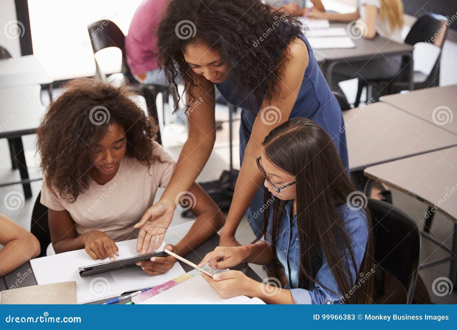 Helfende Studenten des Lehrers mit Technologie, hoher Winkel