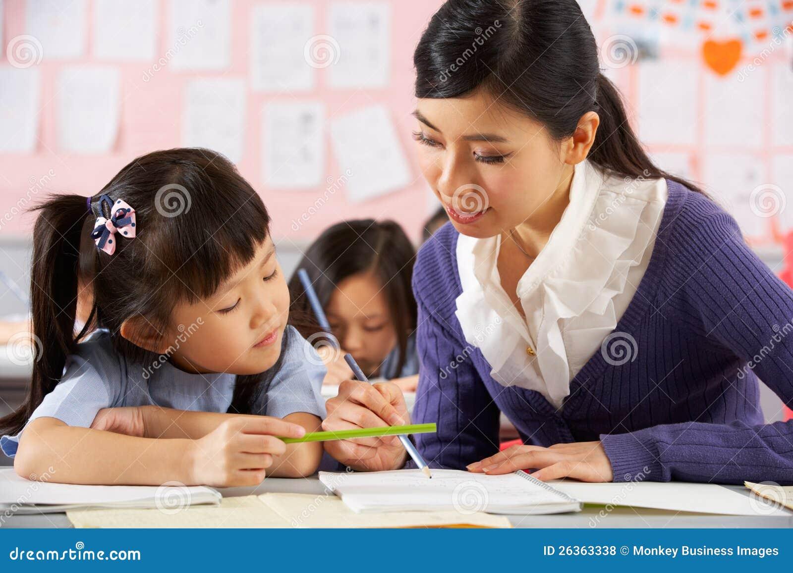 Helfender Kursteilnehmer, der am Schreibtisch in der chinesischen Schule arbeitet