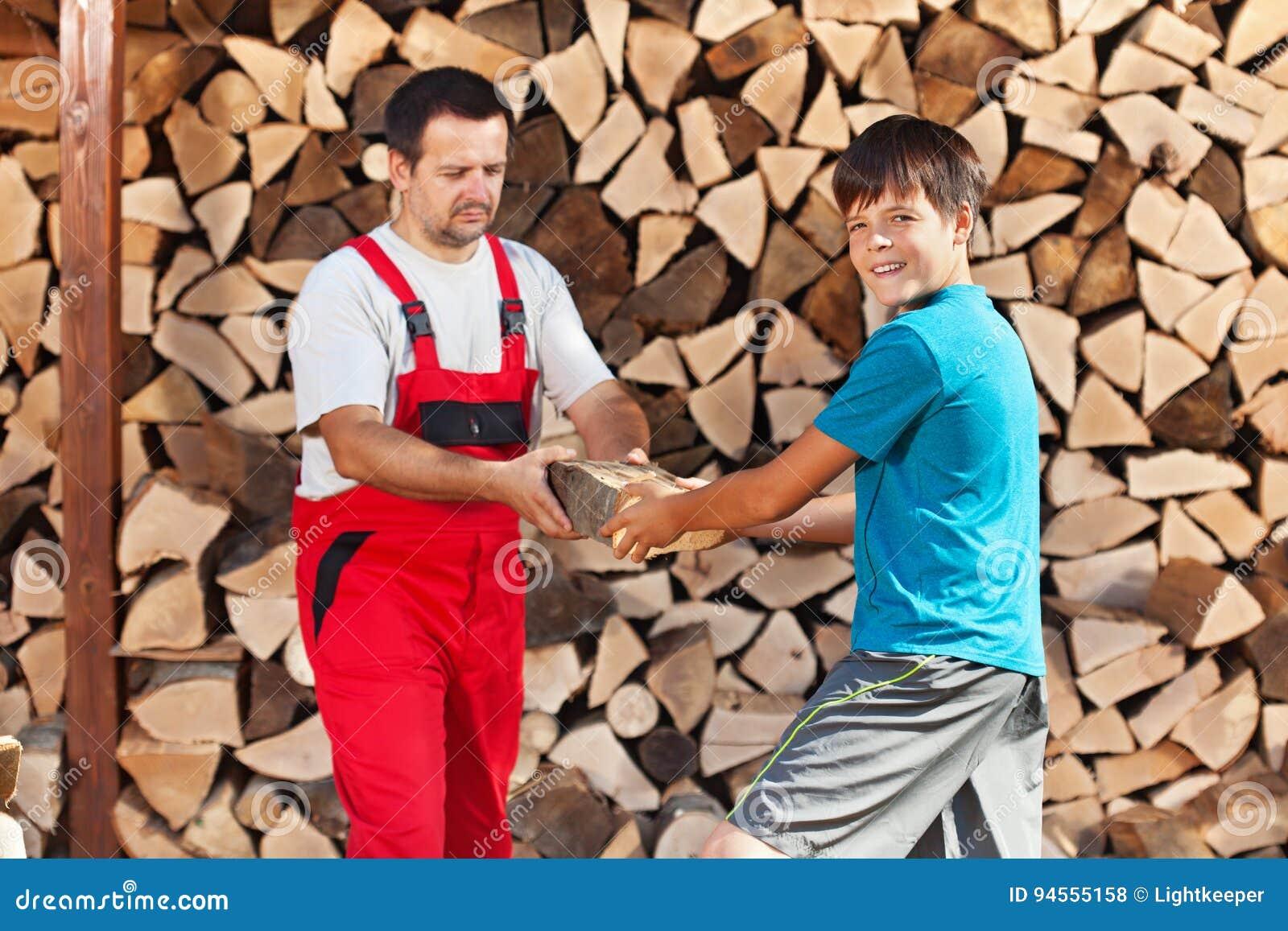 Helfender Vater des Teenagers das Brennholz stapeln