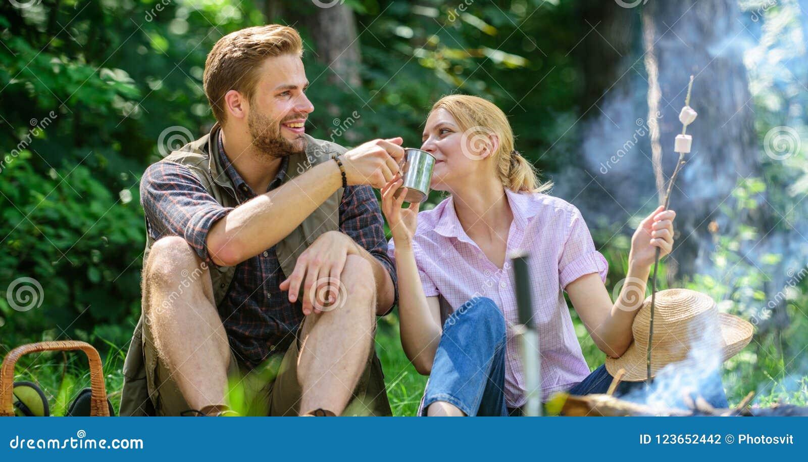 Helgpicknick Mat för vandring och att campa Par sitter nära brasa äter mellanmål och drinken Partagandeavbrott som äter naturen