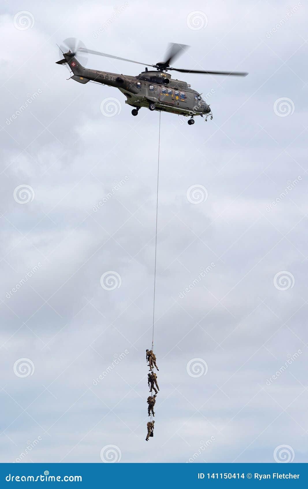Helicóptero de serviço público militar suíço T-340 de Aeroespacial AS532 TH98 da força aérea que transporta tropas pela suspensão