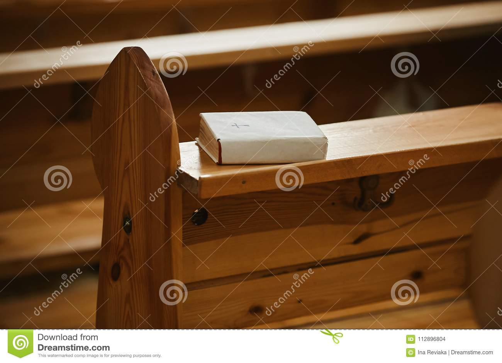 Helig bibel i en vitbokräkning på en träbänk i kyrka