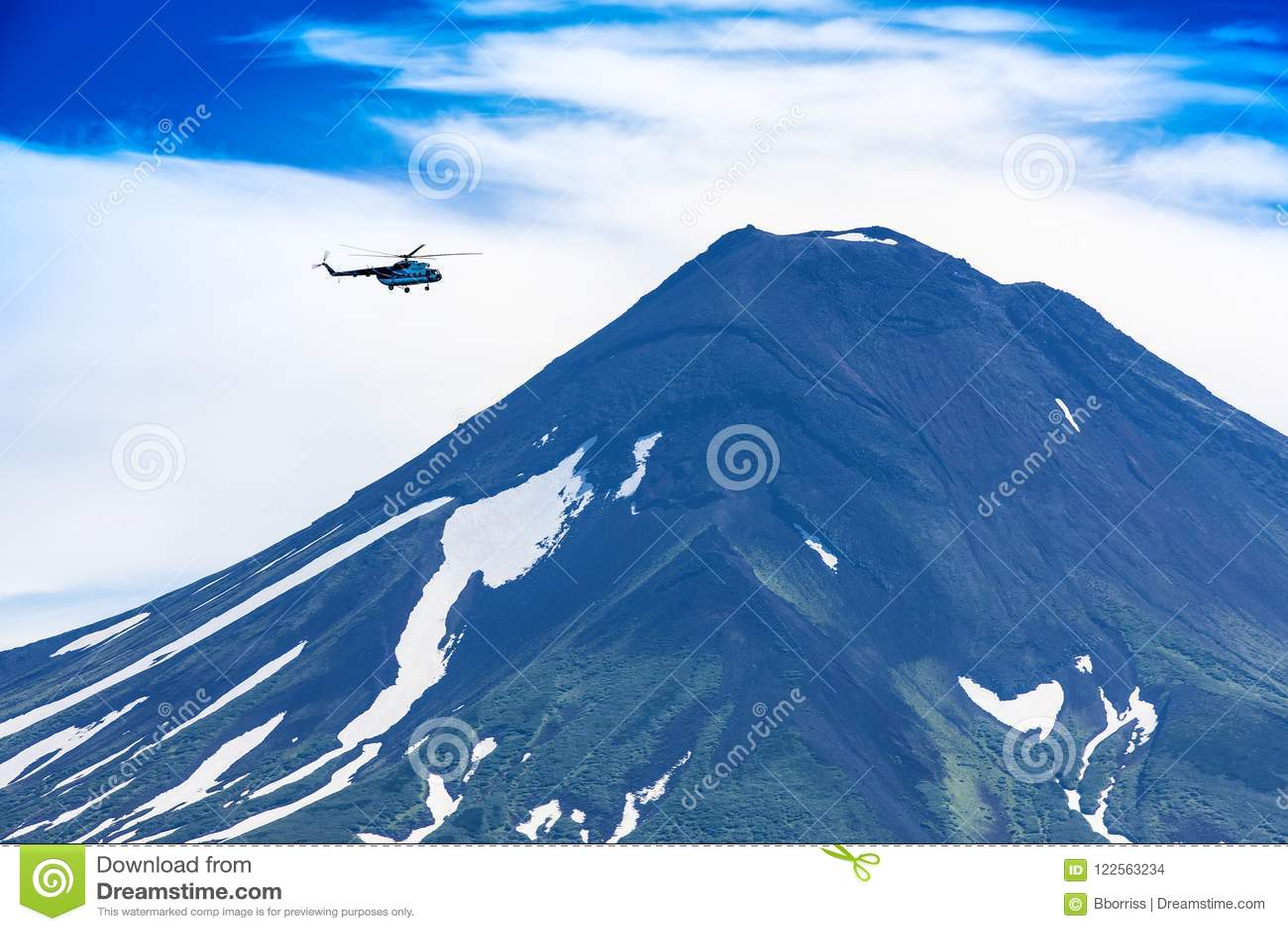 Helikopter die over Ilyinsky-Vulkaan en Kurile-meer vliegen