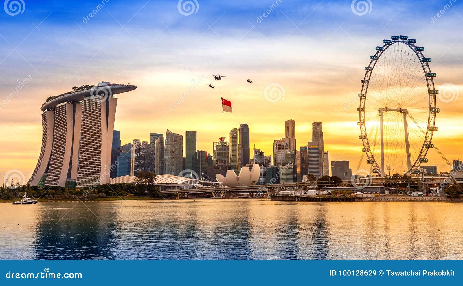 Helikopter Singapore för nationell dag som hänger den Singapore flaggan som flyger över staden
