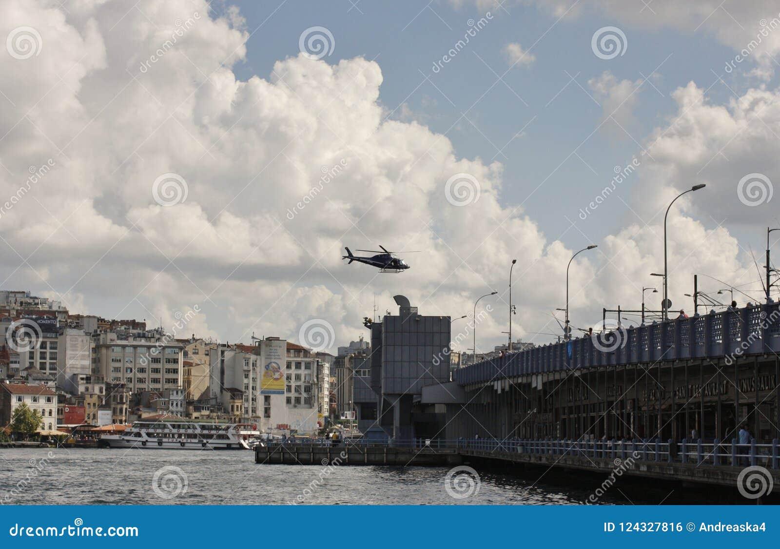 Helikopter som flyger över det guld- hornet och den Galata bron