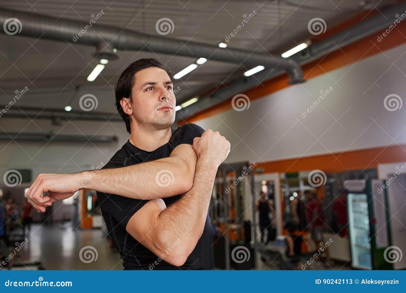 Hellångt av ung man i den svarta sportswearen som sträcker hans arm på idrottshallen