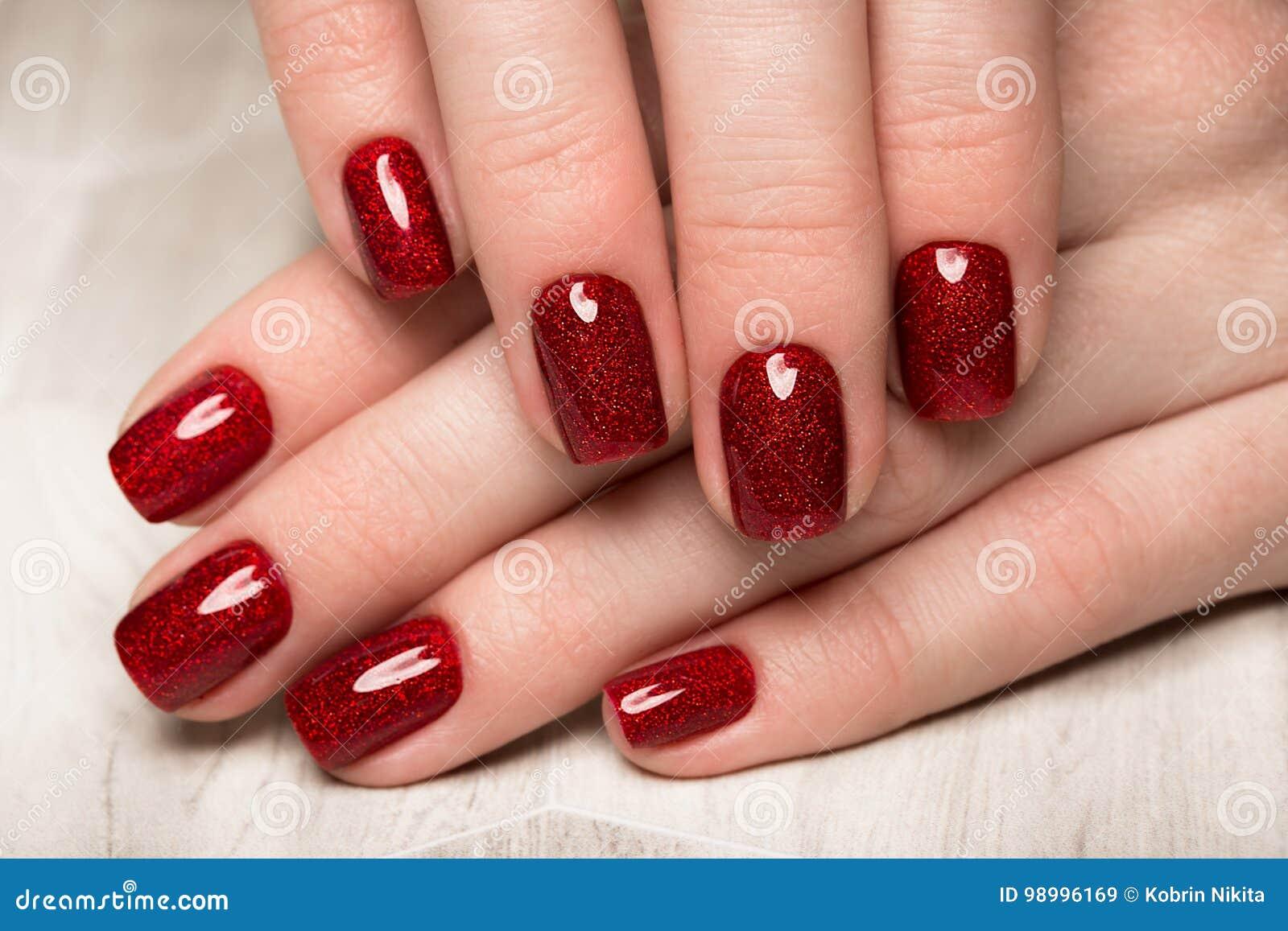 Helle festliche rote Maniküre auf weiblichen Händen Nageldesign