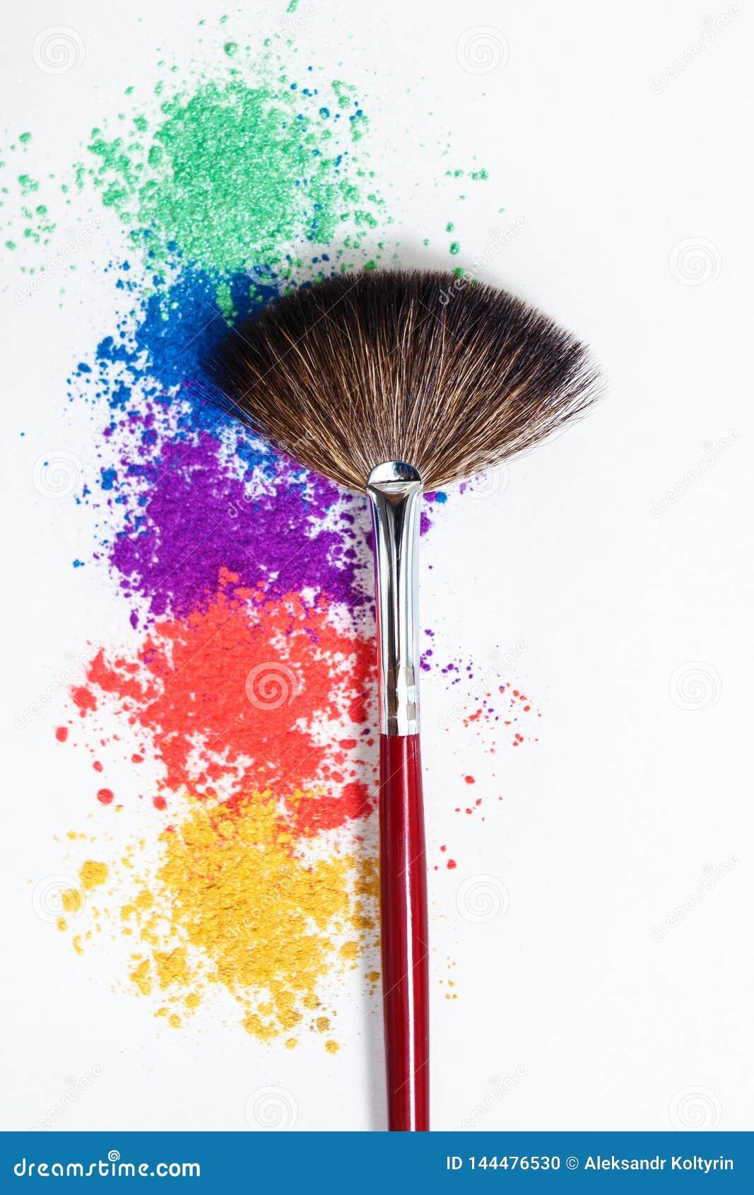 Helle Lidschatten in den verschiedenen Farben des Regenbogens und der B?rsten f?r Kosmetik auf einem wei?en Hintergrund