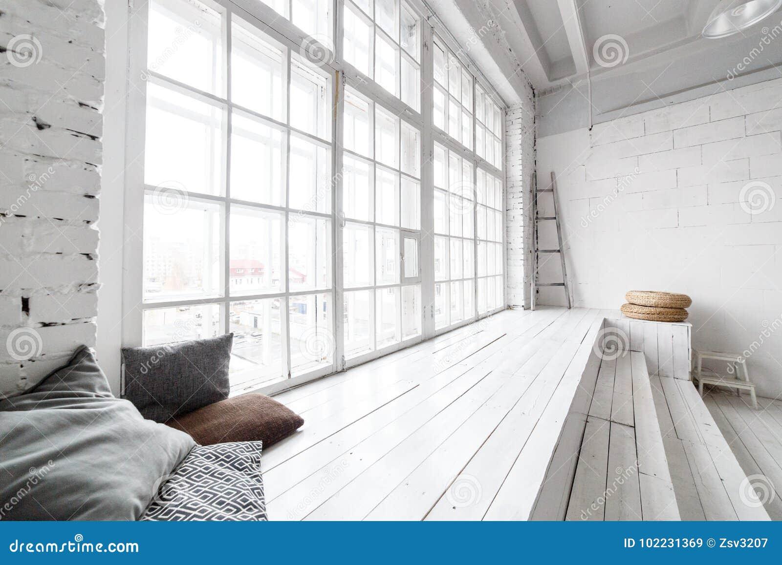 Heller Fotostudioinnenraum mit großem Fenster, hohe Decke, weißer Bretterboden