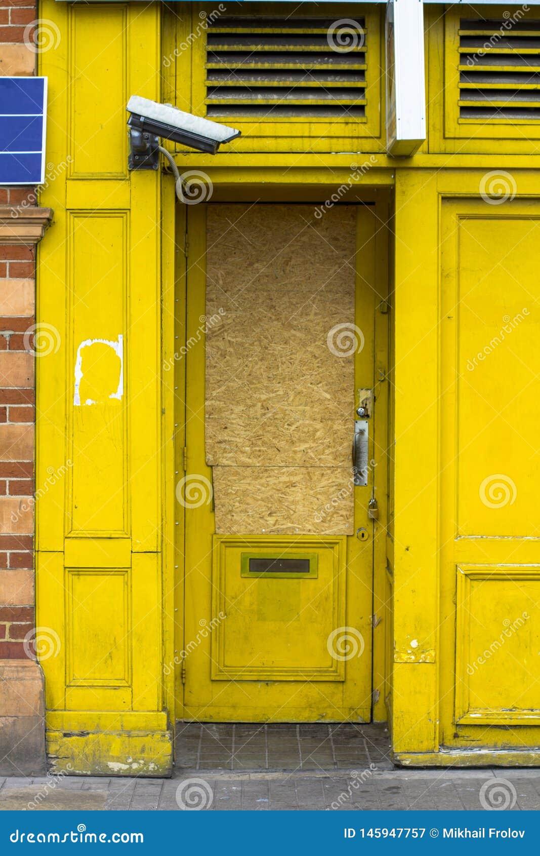 Heller gelber Eingang ?berwachte durch eine Videokamera Eintritt verstopft mit Sperrholz Die gelbe T?r ist geschlossen Sicherheit