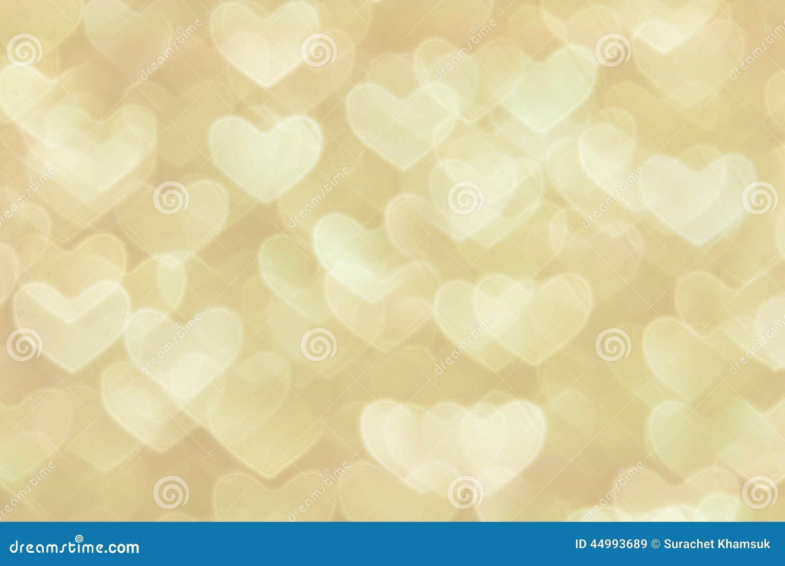 Heller Hintergrund der Defocused abstrakten goldenen Herzen