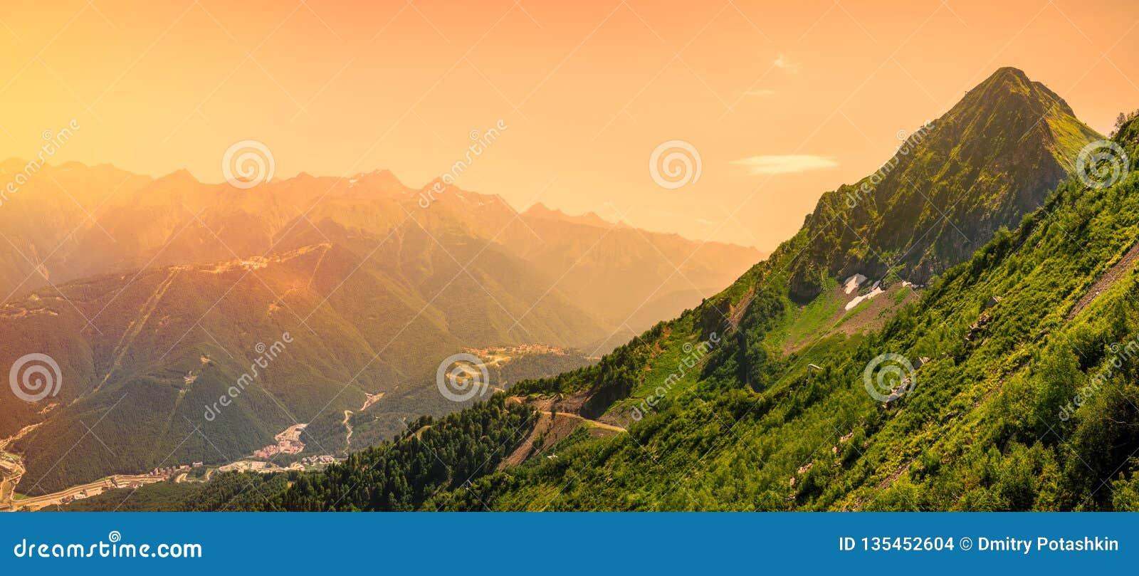Heller Sonnenaufgang in den Bergen Panoramablick des Tales mit Wohngebäuden, umgeben durch Berge mit Drahtseilbahnen