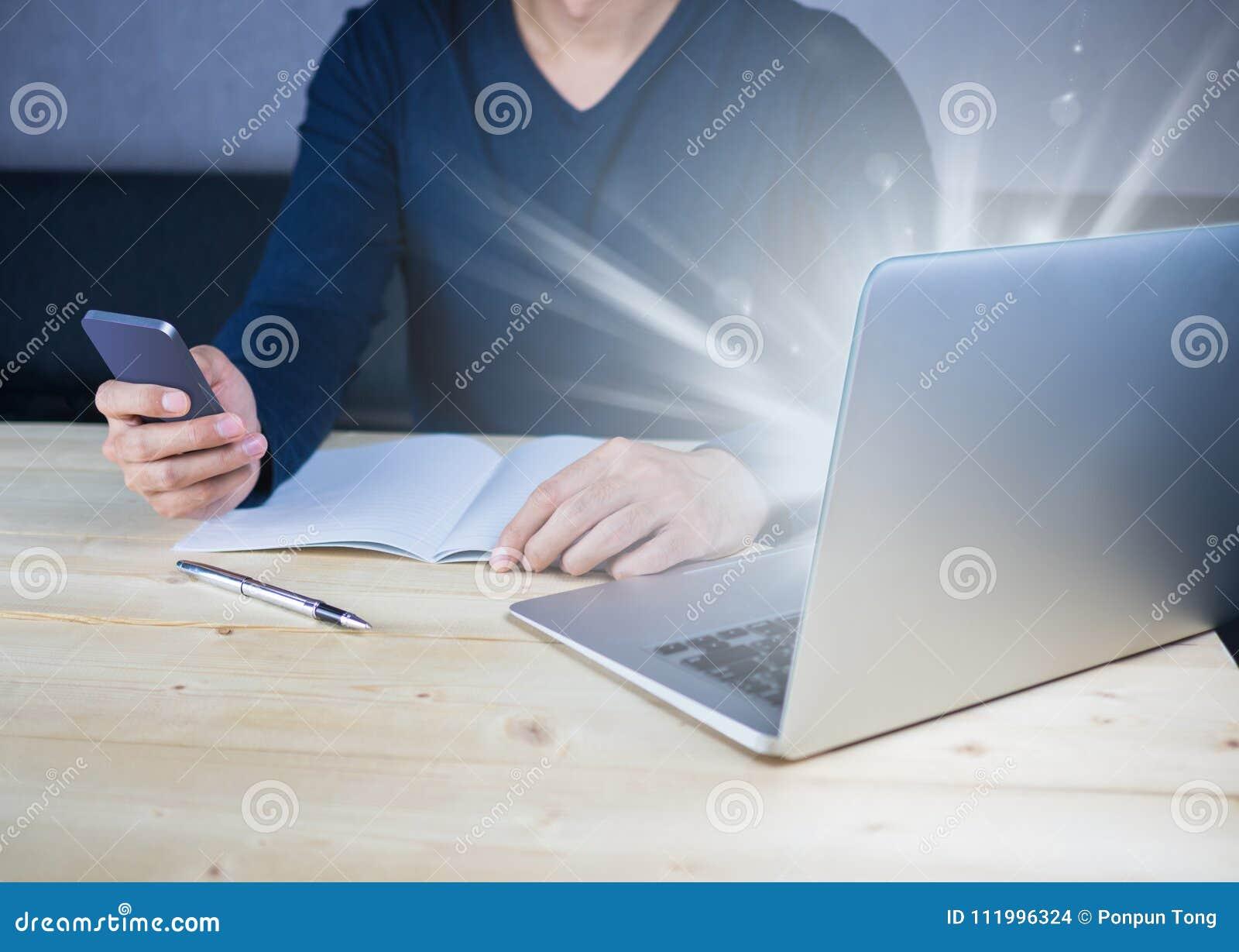 Helles Glühen vom Notebook auf hölzernem Schreibtisch mit der Anwendung von Smartphone