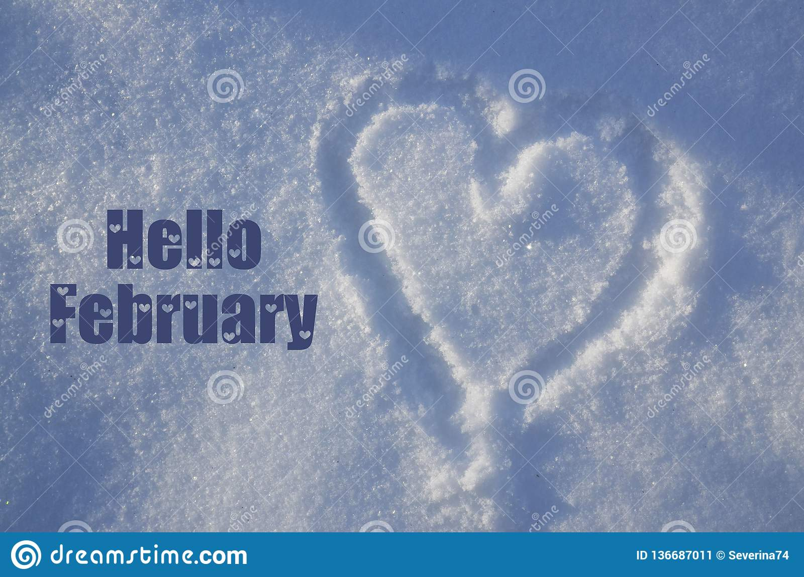 Hello February greeting card with heart drawing on natural white snow on a sunny day.Winter season or Valentines Day concept.