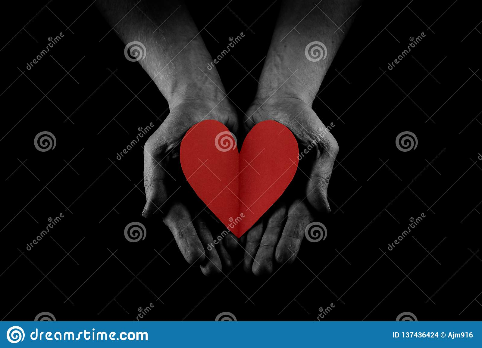 Helping hand concept, Man`s hands palms up holding a Red Heart, giving love, care and support, reaching out