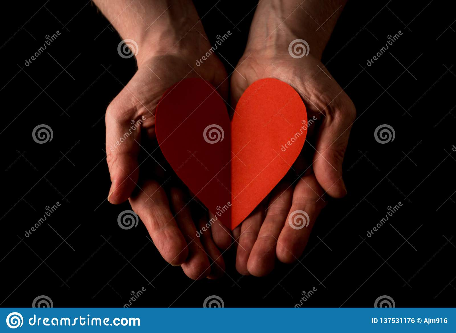 Helping hand concept, Man`s hands palms up holding a Red Heart, giving love, reaching out
