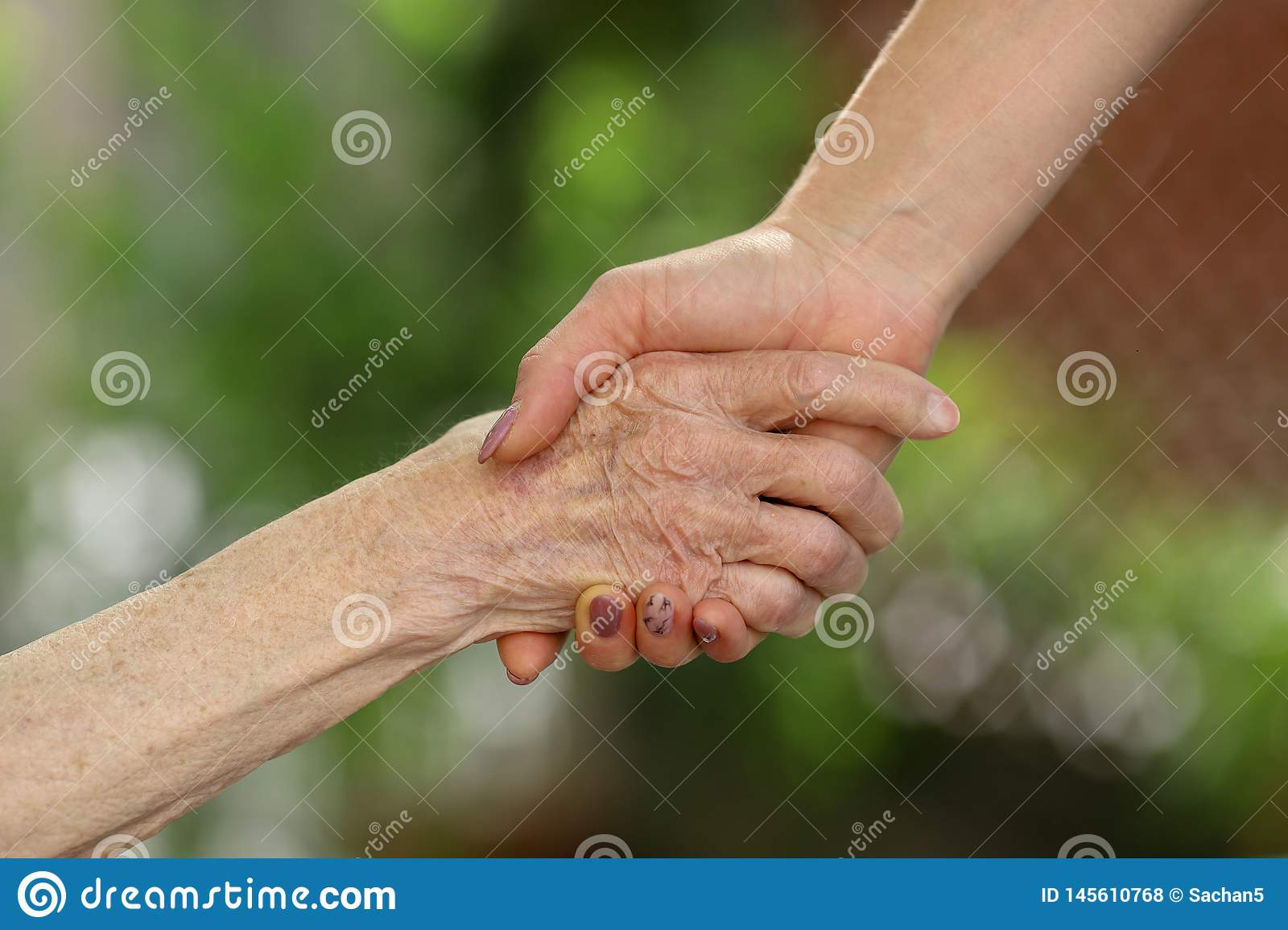 Young caregiver holding seniors hands. Helping hands, care for the elderly concept