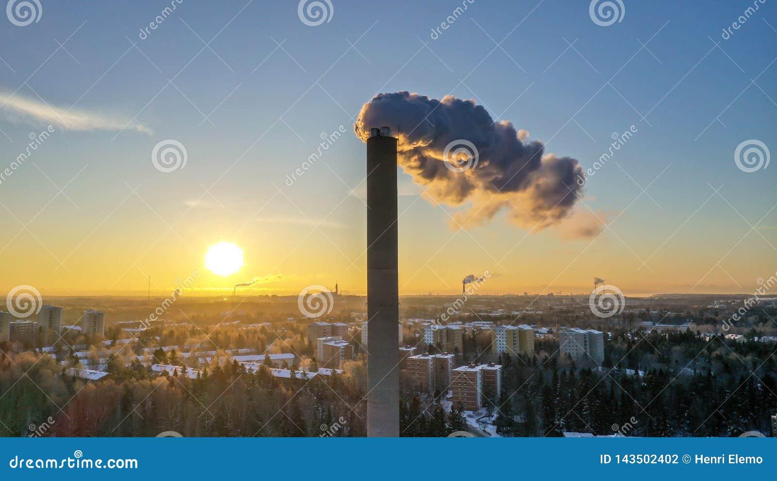 Helsínquia, Finlandia - 21 de janeiro de 2019: Fumo que sai da tubulação da planta de energia em Helsínquia no tempo do por do so