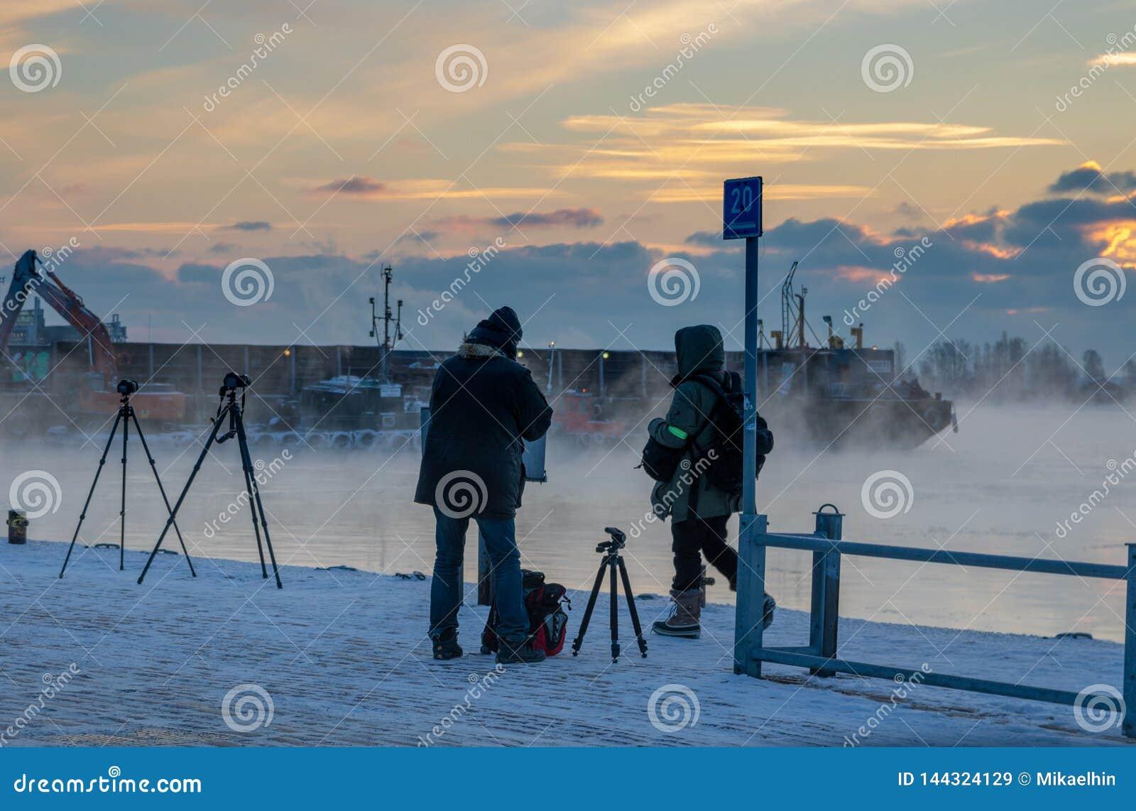 HELSINKI, FINLAND - JANUARY 8, 2015: Freezing photographers at harbor in winter