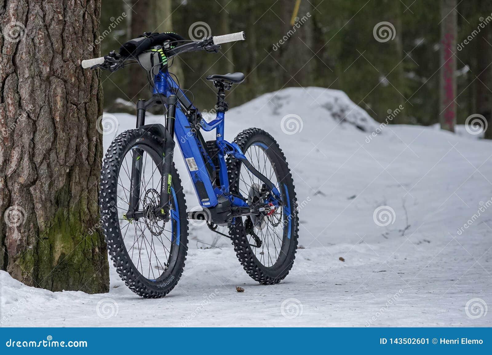 Helsinki, Finlande - 13 mars 2019 : Position électrique de vélo de montagne contre l arbre sur la terre neigeuse à Helsinki