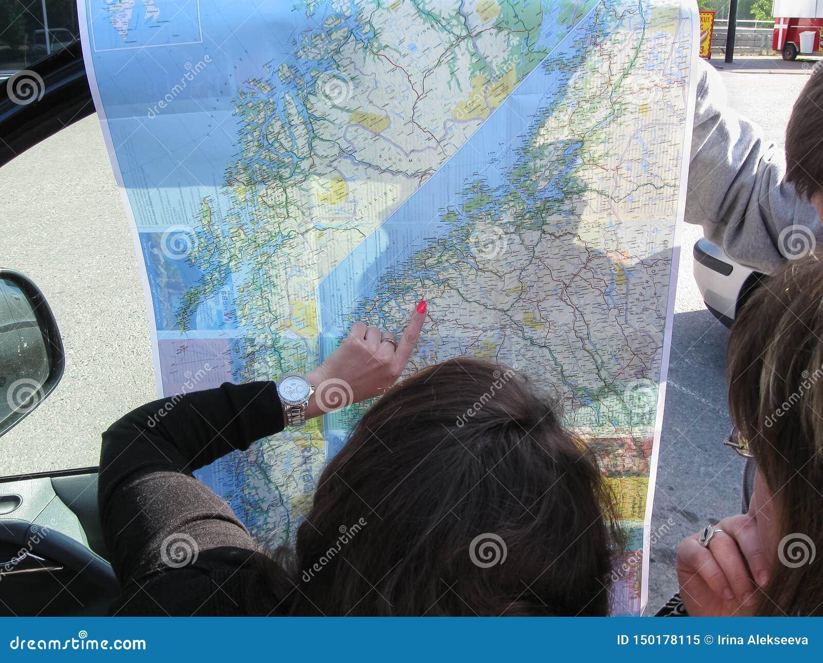 Helsinki, Finlandia - 11 06 2012: los turistas ven el mapa y componen la ruta