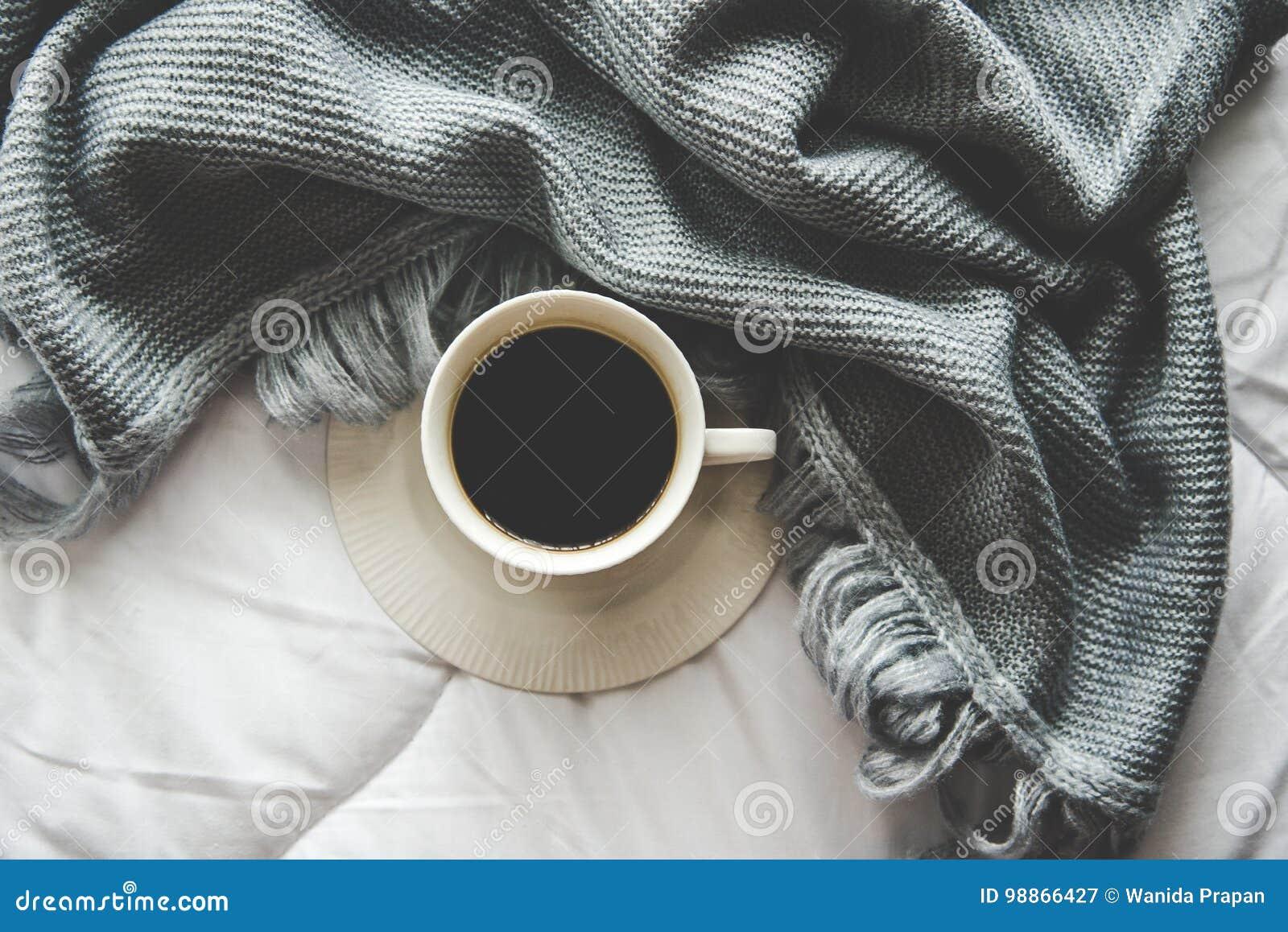 Hem- bakgrund för hemtrevlig vinter, kopp av varmt kaffe med marshmallowen, varm stucken tröja på vit sängbakgrund, tappningsigna