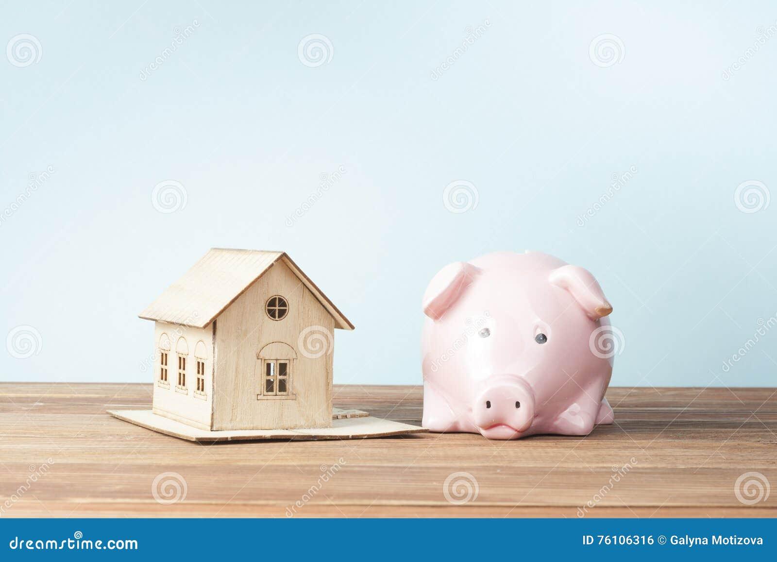 Hem- besparingar, budget- begrepp Modellera huset, notepaden, pennan, räknemaskinen och mynt på den trätabellen för kontorsskrivb