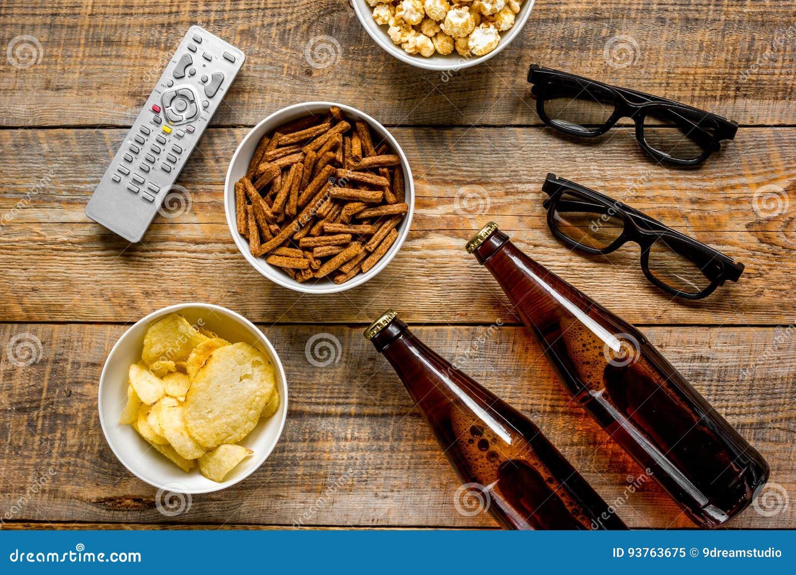 Hem- parti med TVatt hålla ögonen på, mellanmål och öl på bästa sikt för träbakgrund
