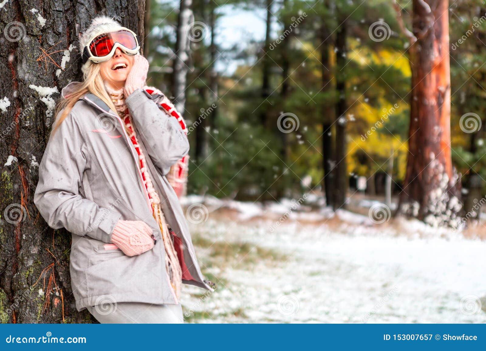 Hembra alegre en un bosque nevoso del arbolado del invierno
