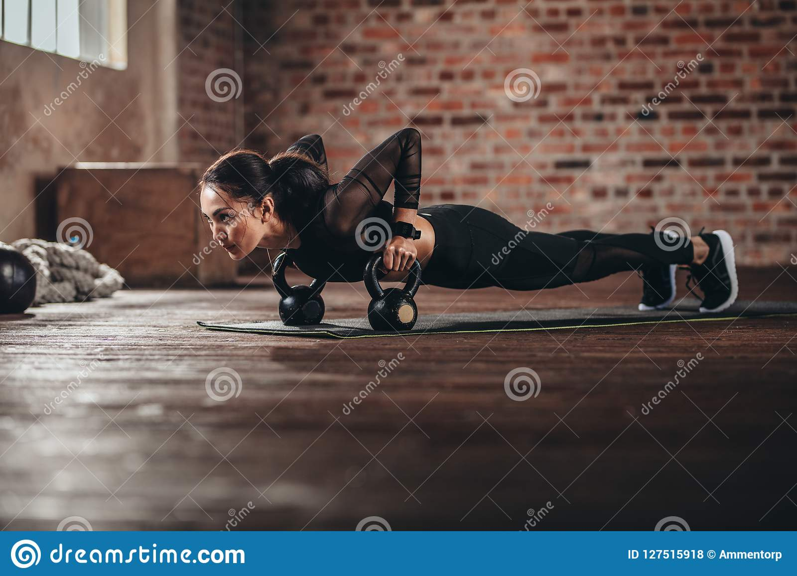 Hembra apta que hace entrenamiento intenso de la base en gimnasio