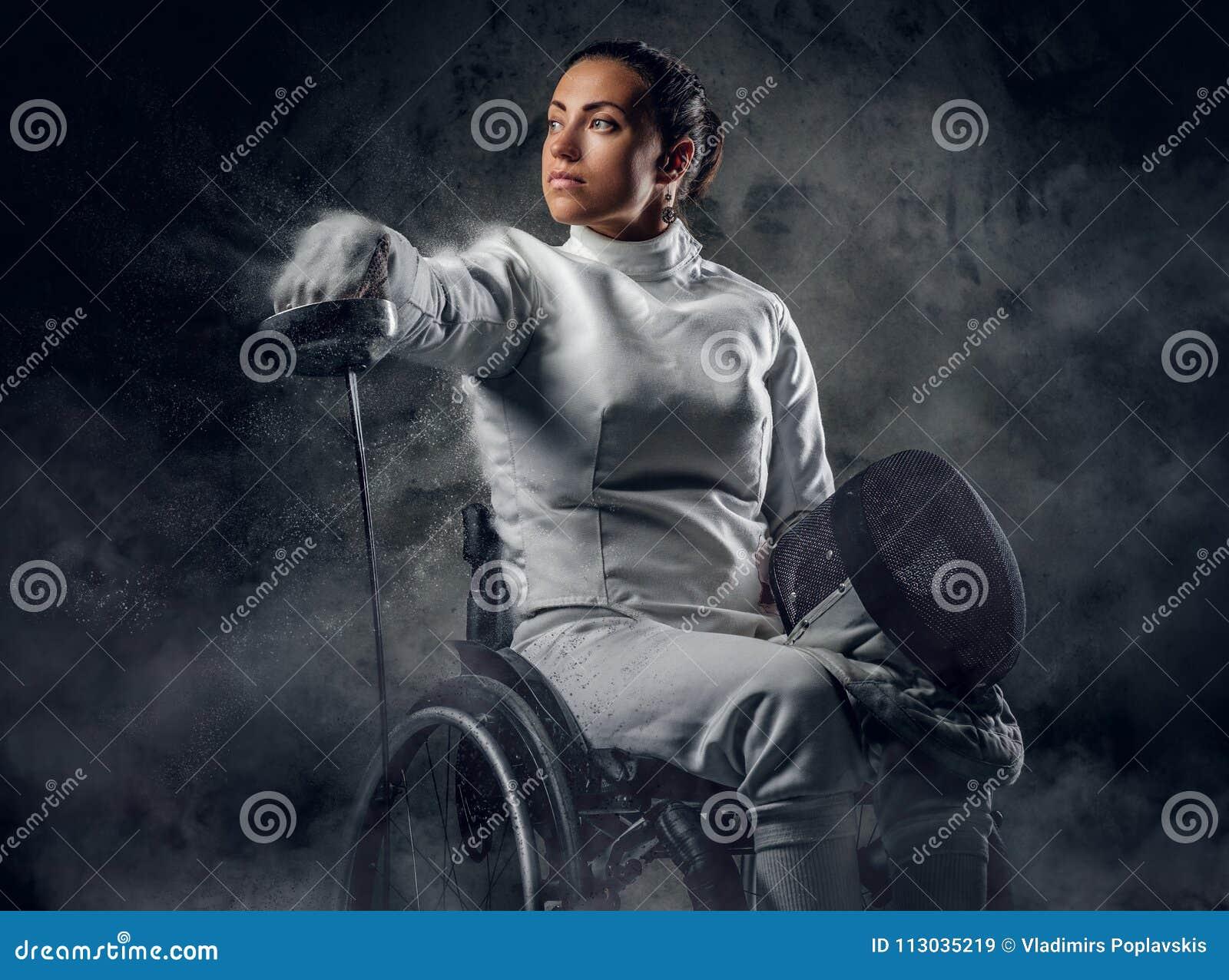 Hembra en silla de ruedas con la máscara de la seguridad de una cara que sostiene el estoque