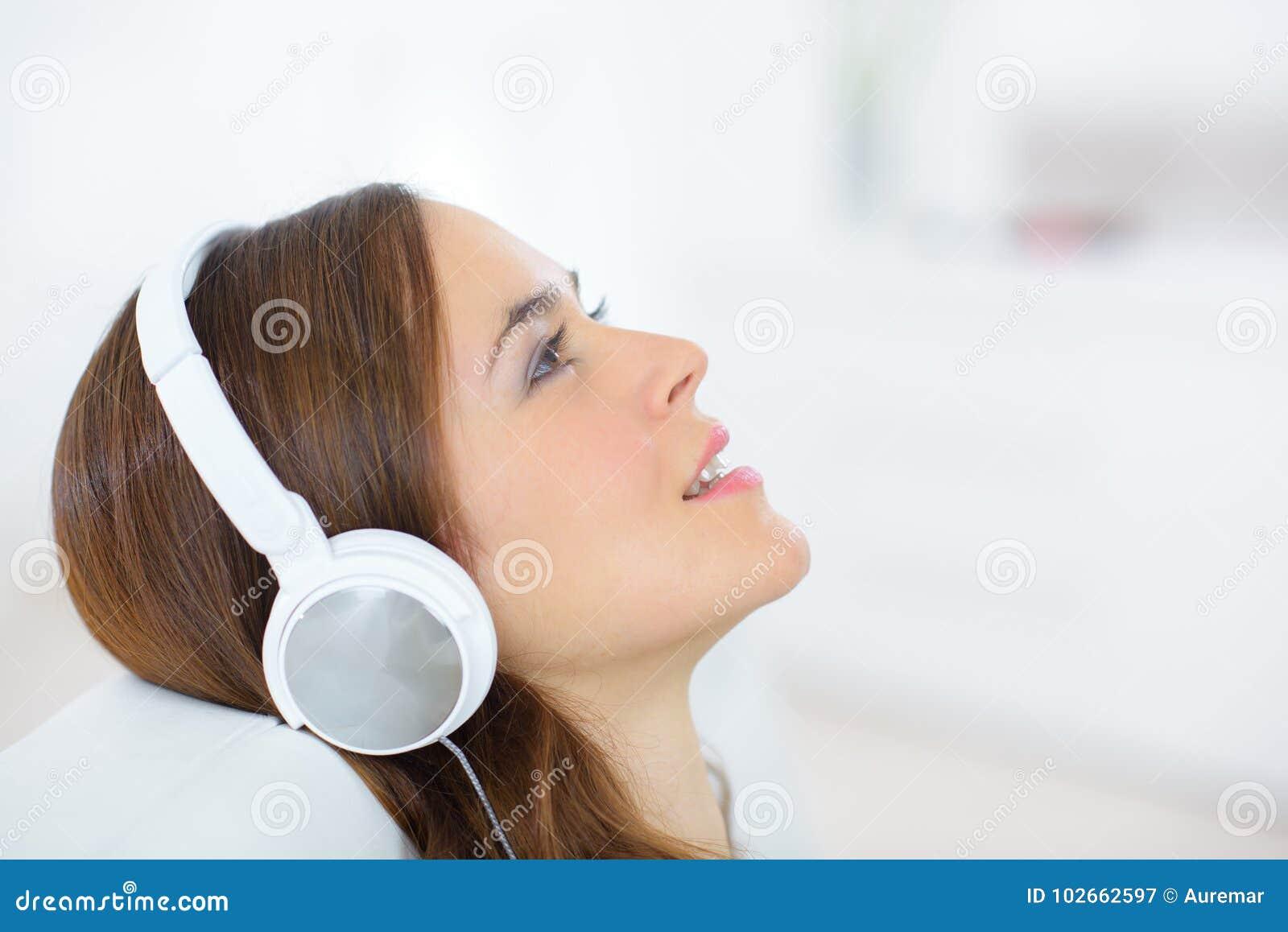 Hembra joven atractiva del retrato del primer con los auriculares