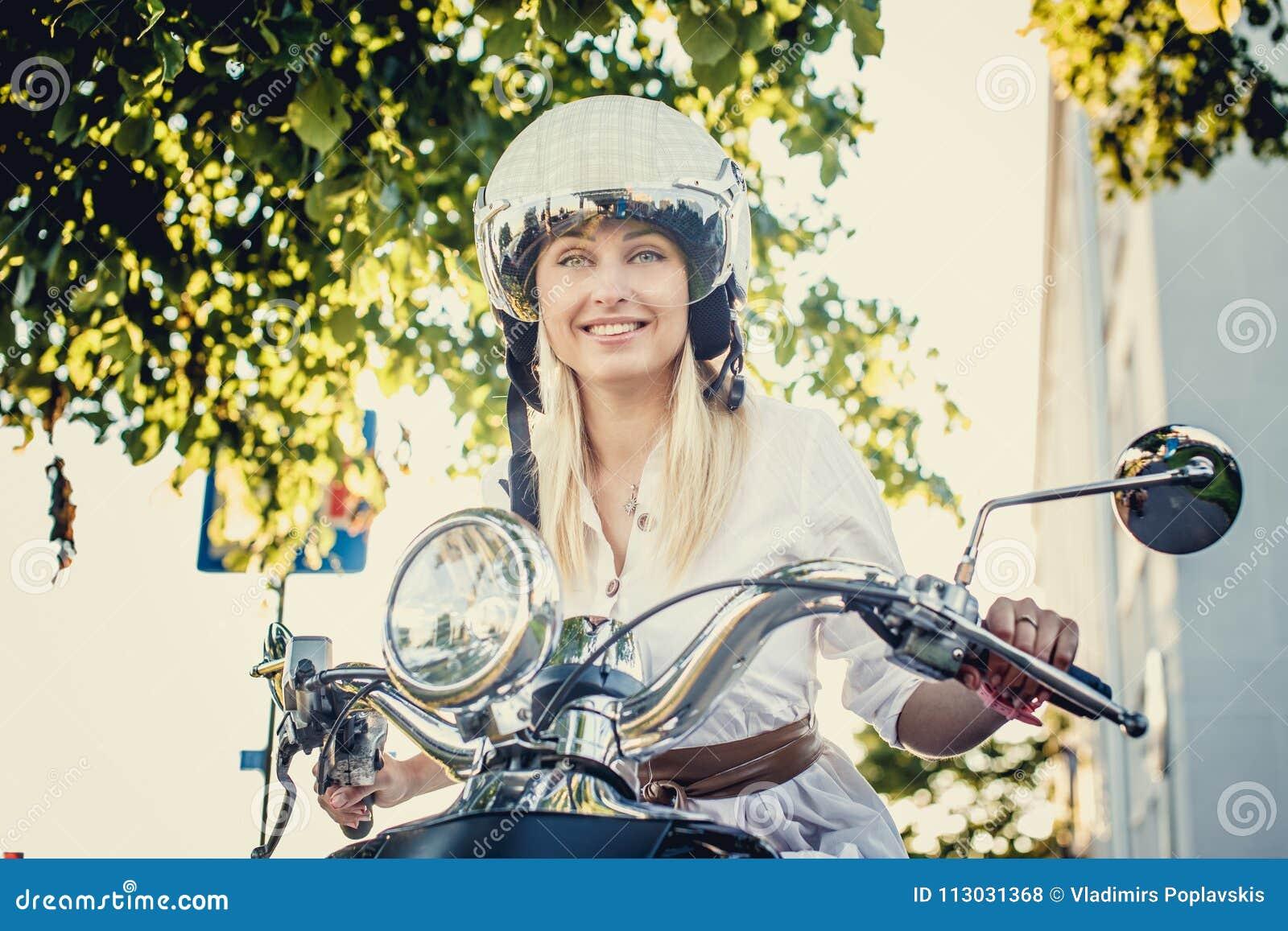 Hembra rubia sonriente en vaqueros, camiseta y casco