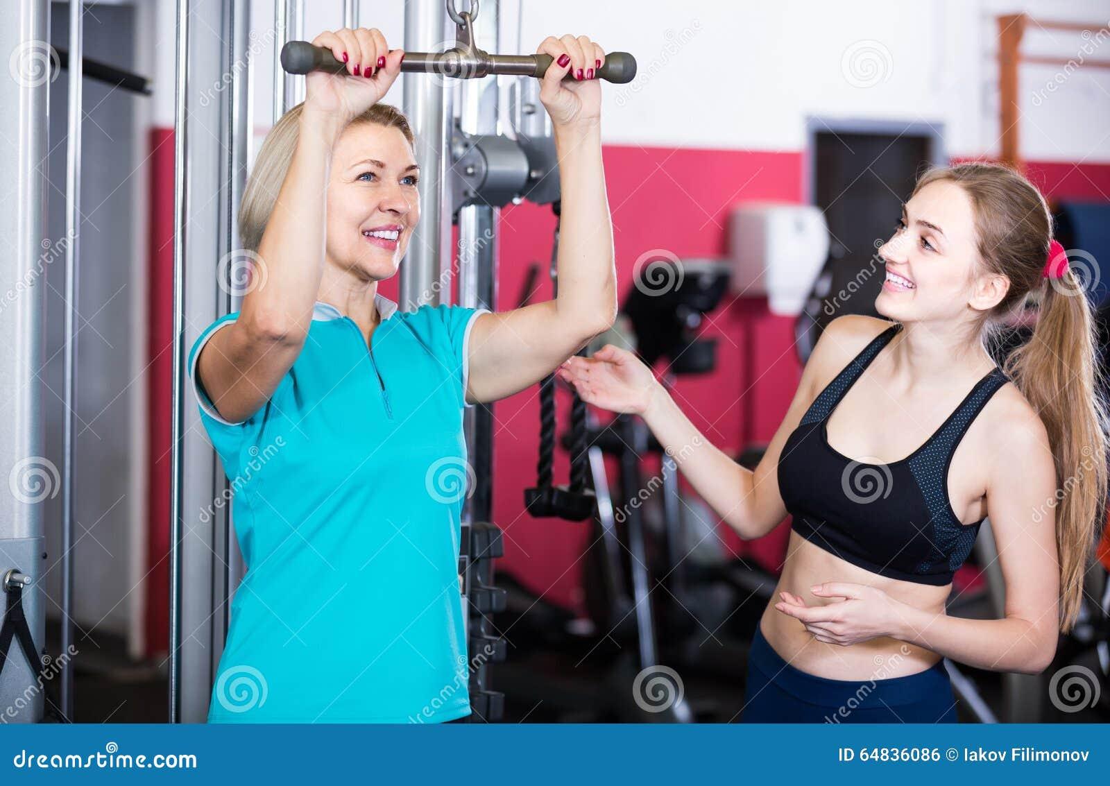 Hembras de diverso entrenamiento de la fuerza de la edad en gimnasio