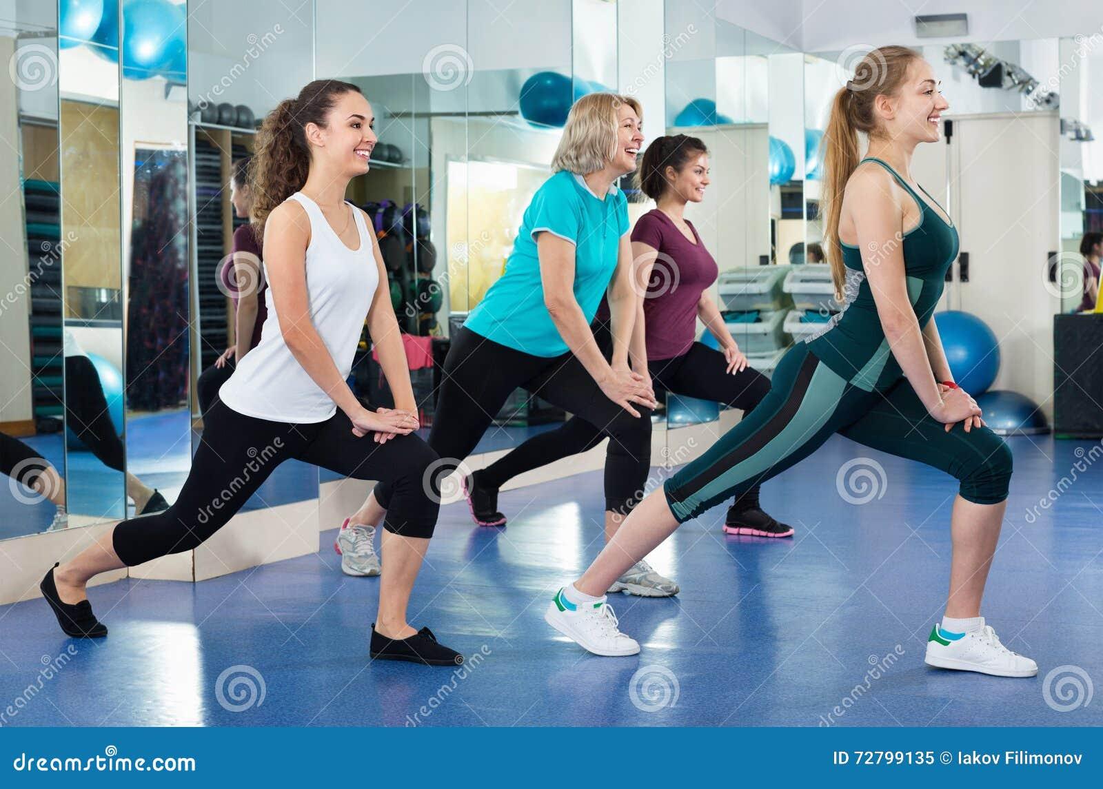 Hembras positivas que se resuelven en la clase aerobia en gimnasio moderno