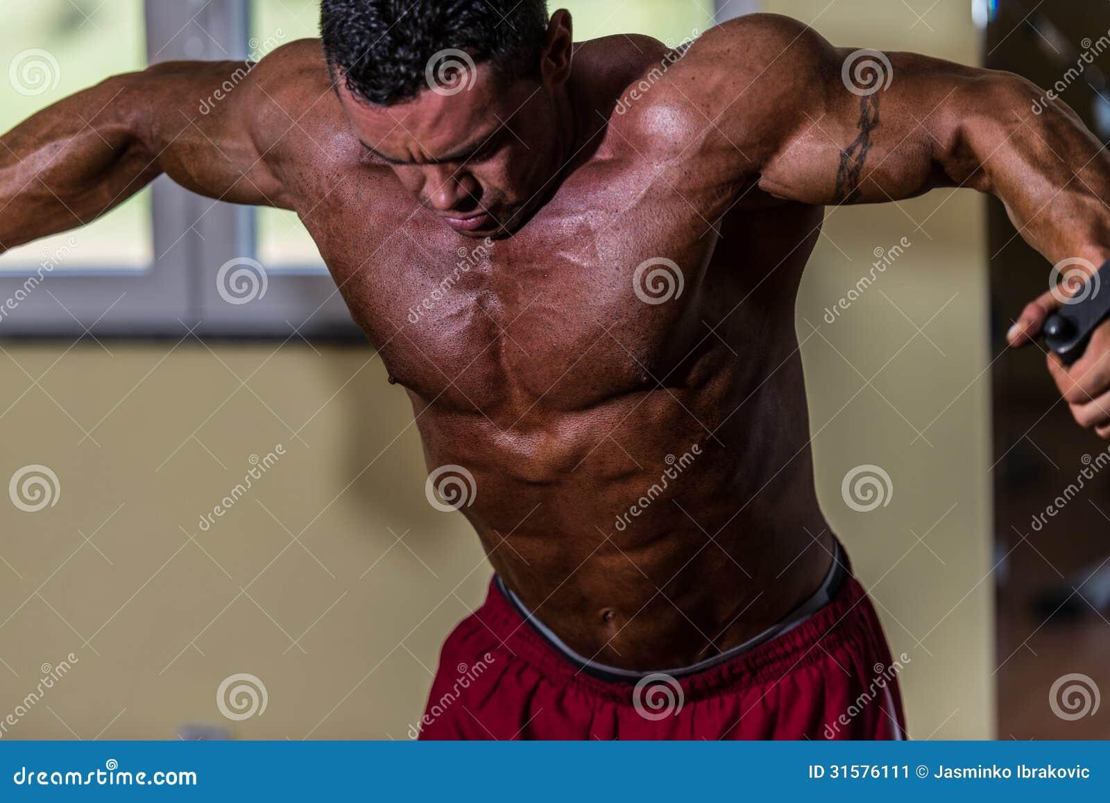Hemdloser Bodybuilder, der weißes Kabel der stehenden Presse für Kasten tut