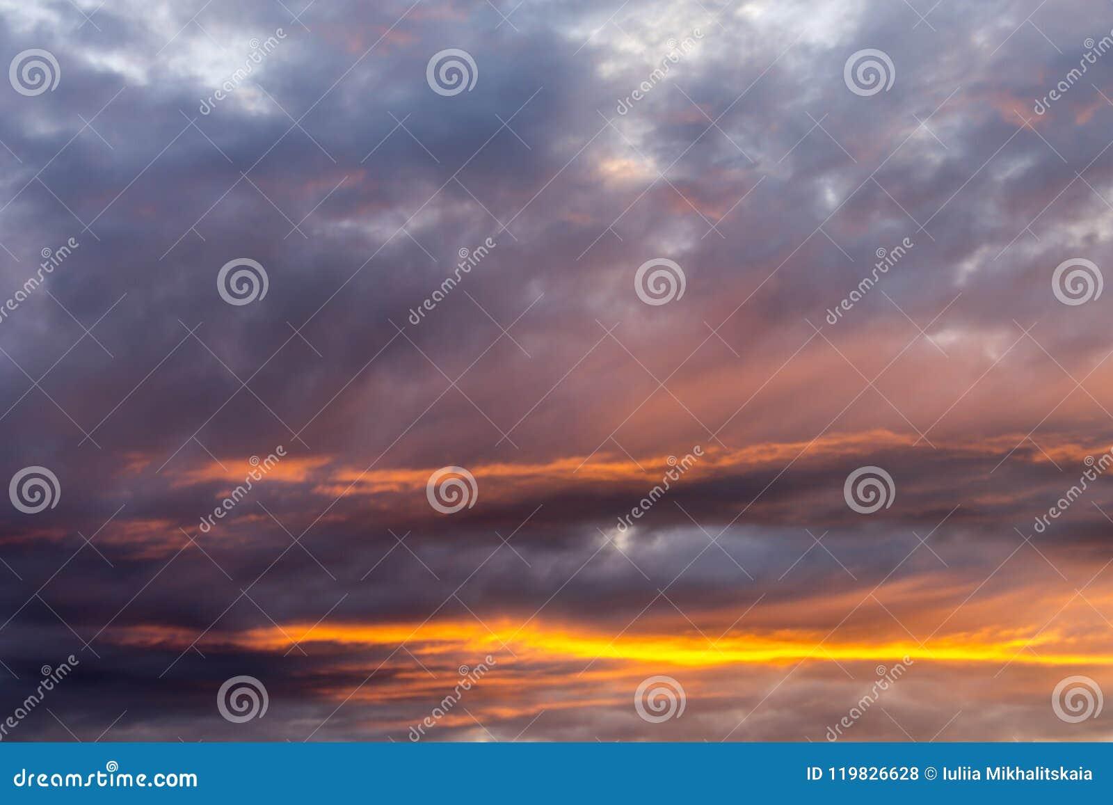 Hemel met grijze en blauwe wolken en rood-oranje hoogtepunt van de Zon, achtergrond