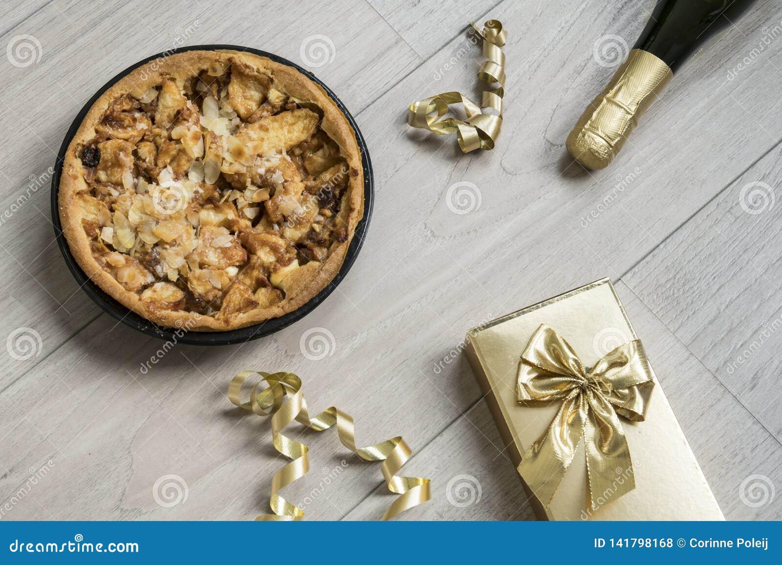 Hemlagad äppelpaj, med guld- gåva och flaskan av champagne