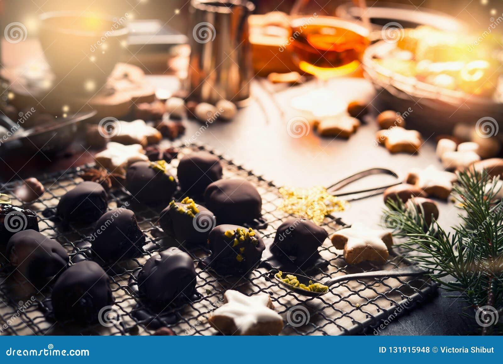 Hemlagad festlig konfekt, brända mandlar och tryfflar på mörk lantlig bakgrund med ingredienser Julsötsakbakelser