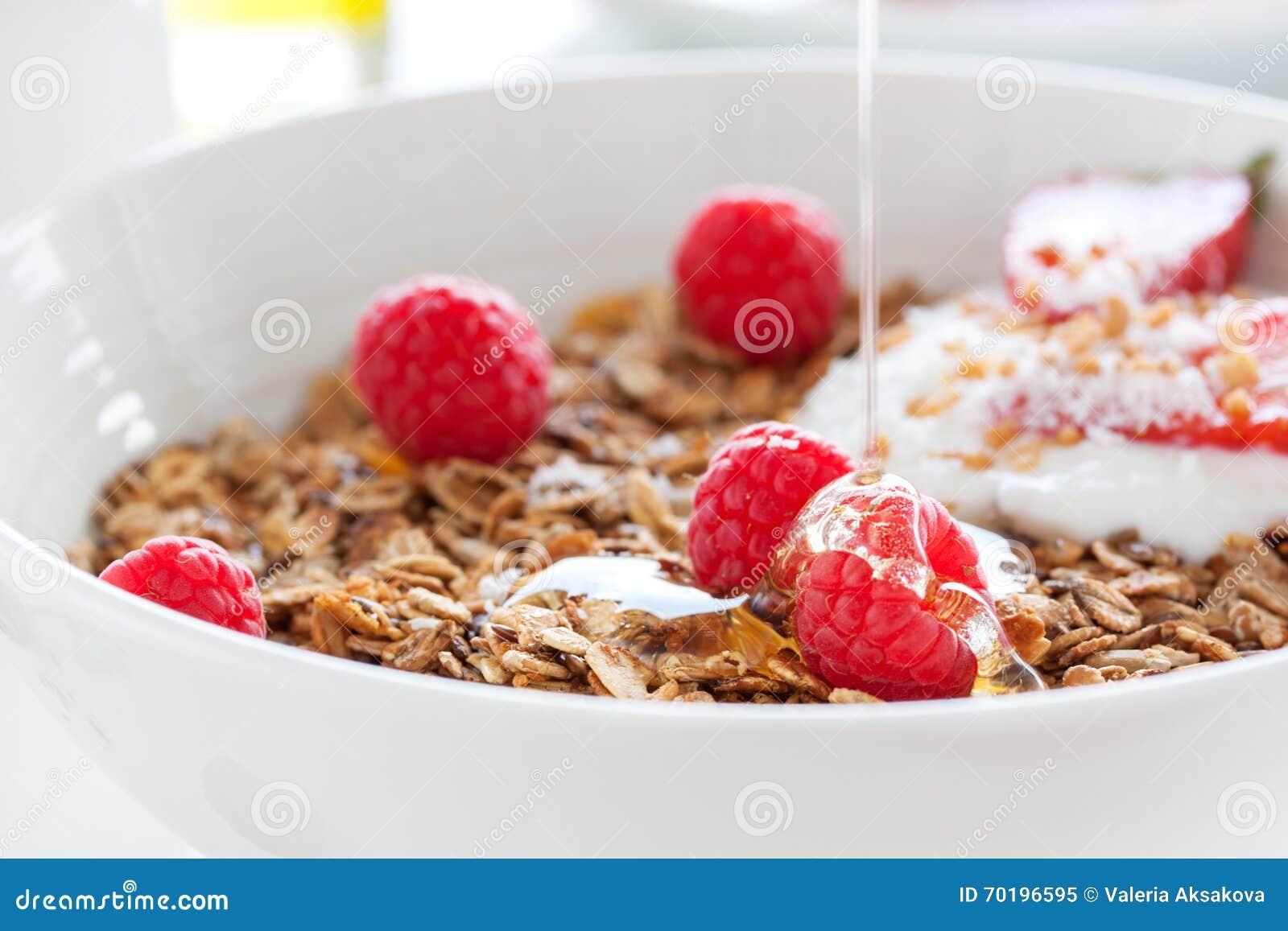 """Hemlagad havremålgranola eller mysli med hallon och jordgubbe med yoghurt och honung för ny sommarfrukt†""""i en vit bunke"""