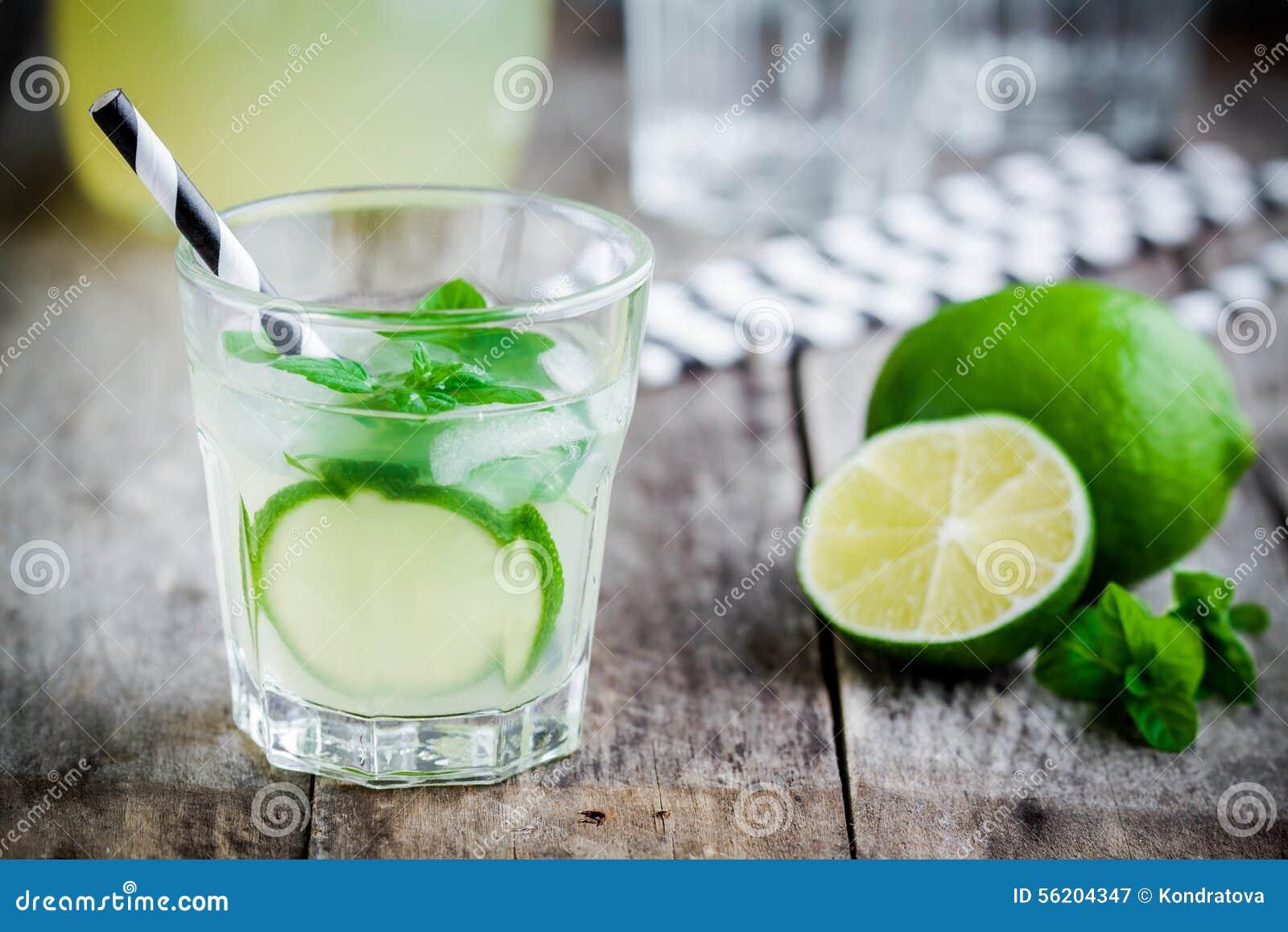 Hemlagad lemonad med limefrukt, mintkaramellen och is på en trätabell