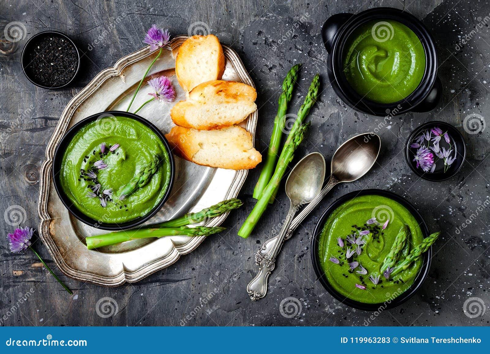 Hemlagade gröna vårsparriers lagar mat med grädde soppa som dekoreras med svart sesamfrö, och ätliga gräslökar blommar